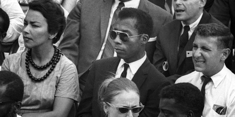 Photograph of James Baldwin, in suit and tie with sunglasses, sitting in an audience, watching something.