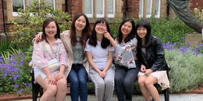 5 MA students who completed the Student into Schools Go Global Scheme sat on a bench on campus
