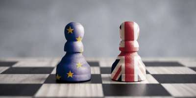 Chessboard with two chesspieces - one painted with the EU flag, the other with the Union Jack.